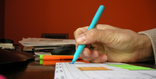A picture of a hand holding a teal highlighter over a piece of paper.