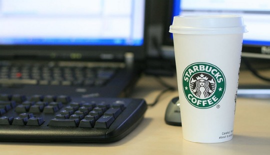 A Starbucks cup next to a computer screen and keyboard